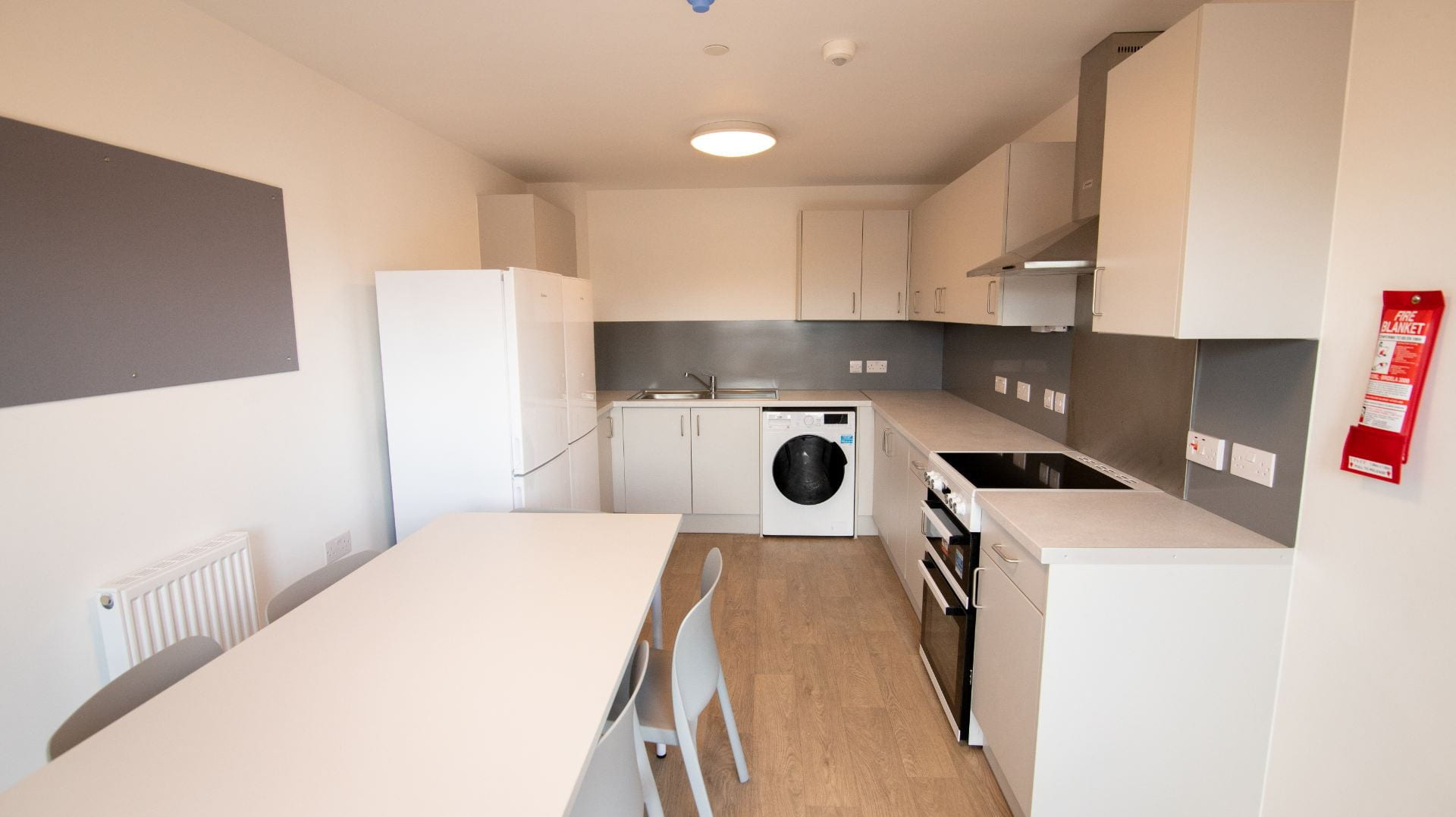 Valentine Court kitchen showing table and chairs, kitchen cupboards, fridge freezers, pin boards, oven and washing machine.