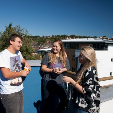 3 Students chatting on Lincoln Courts Balcony