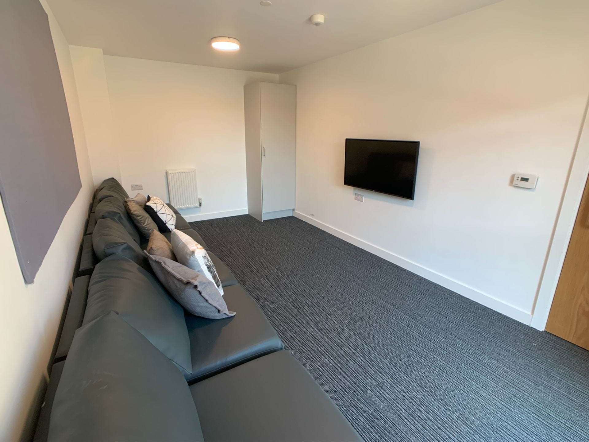 Valentine Court lounge showing sofa's and TV.