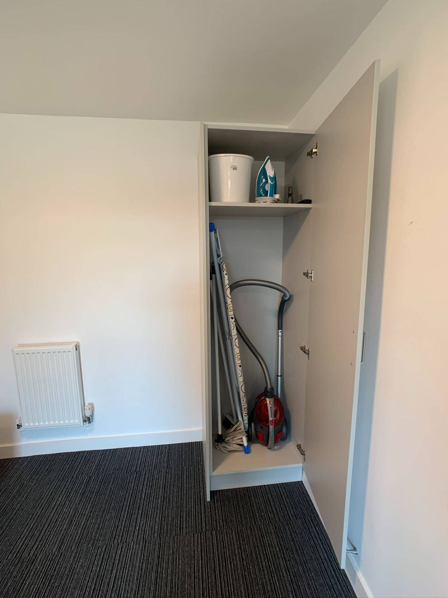 Valentine Court lounge showing communal cupboard including hoover, mop and bucket.