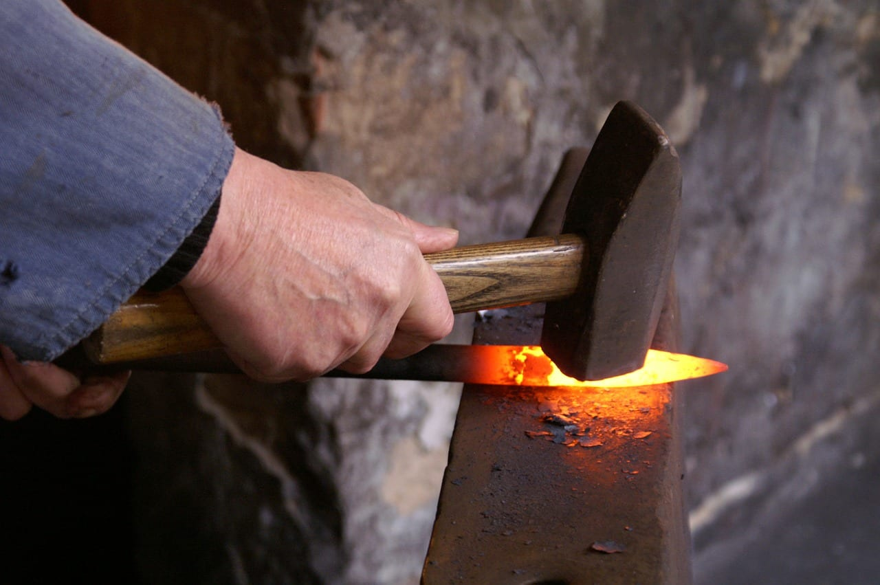 Hammering hot metal on an anvil in a forge