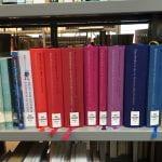 A rainbow-coloured row of books in dutch