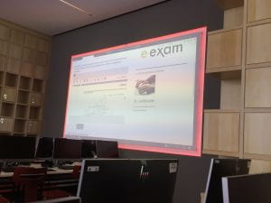 A large projector screen with e-examinations information on it in a room full of computers