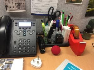 A picture of a telephone headset and stationary caddy with a red nose next to it.