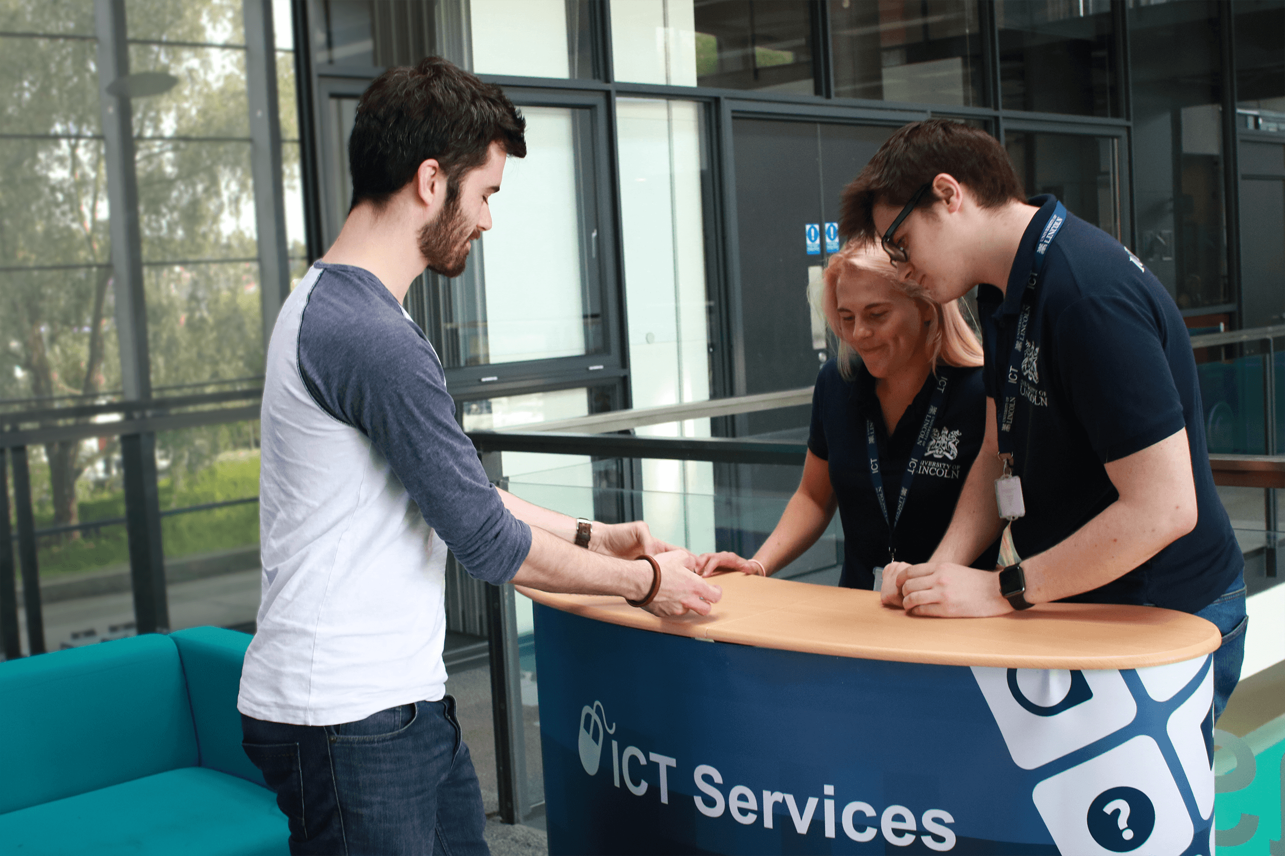 Two ICT student staff members on the roadshow stand assisting a user.