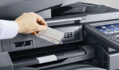 Someone scanning an ID card to log in to a printer.
