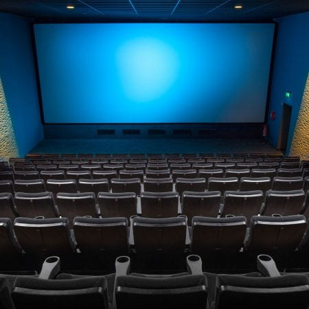 A cinema screen with empty chairs