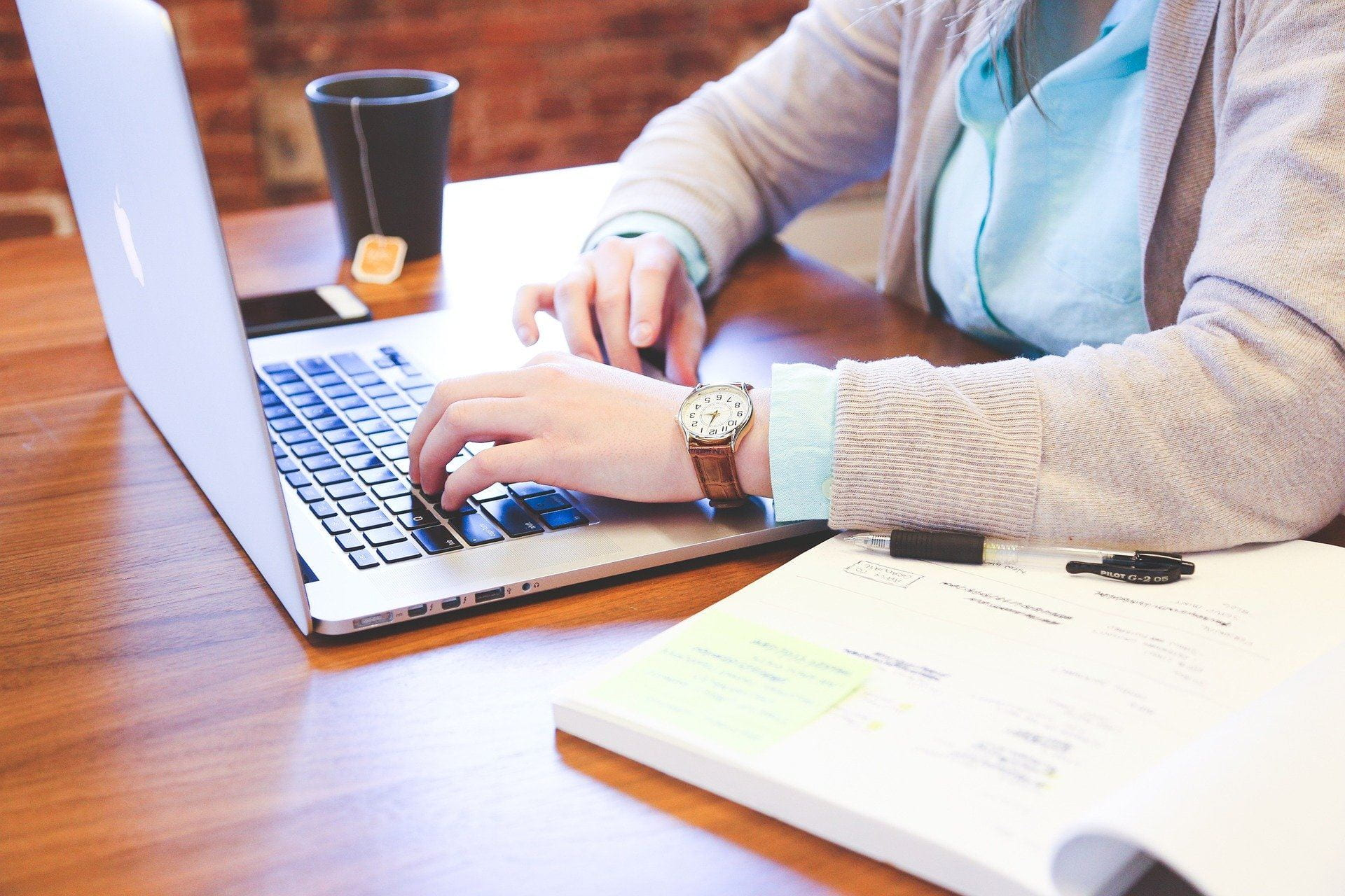 Decorative: [Image Description:] A woman's hands can be seen writing on a laptop. She has a text book open next to her and a cup of coffee can be seen on the end of the table.