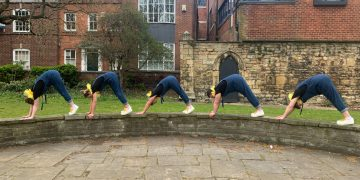 Five performers in dungarees perform an 'on all fours' elephant walk along a low stone wall.