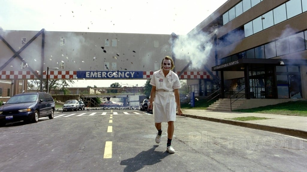A man in a hospital gown wearing smudged clown make up walks away from a hospital explostion