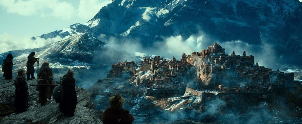 In the distance the ruins of a mountainside town can be seen, shrouded in smoke.