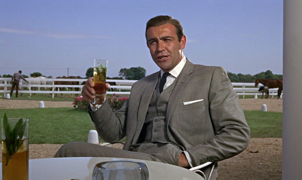 Sean Connery as James Bond, sitting in a chair drinking an alcoholic drink.