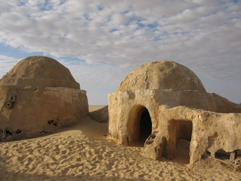 A domed hut is shown with sand creeping up the already decayed walls.