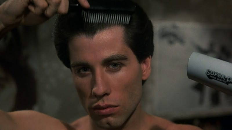 Image featured is a still from the movie Saturday Night Fever. Pictured is John Trovolta combing and blow drying his hair in the mirror.