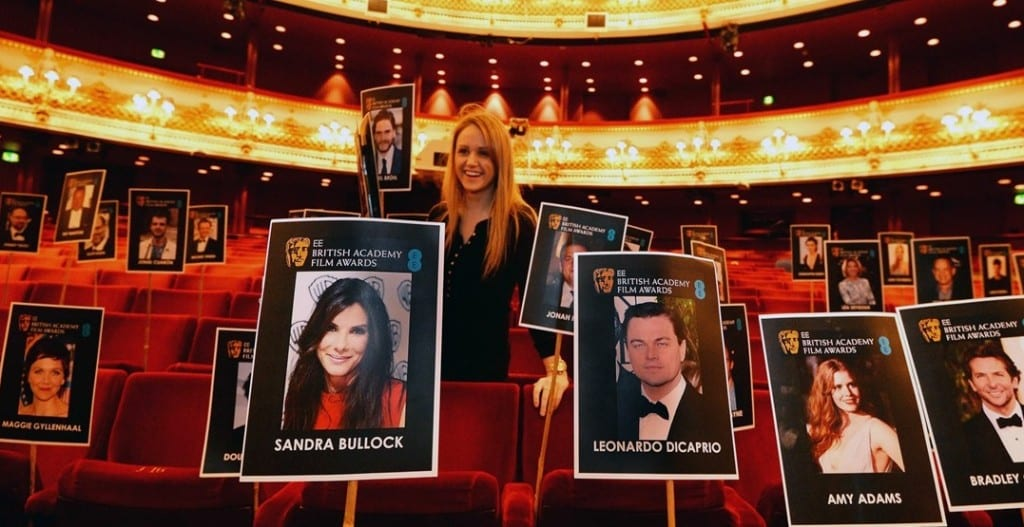 A young blonde woman places signs with showing BAFTA nominees in the red seats at the Royal Opera House