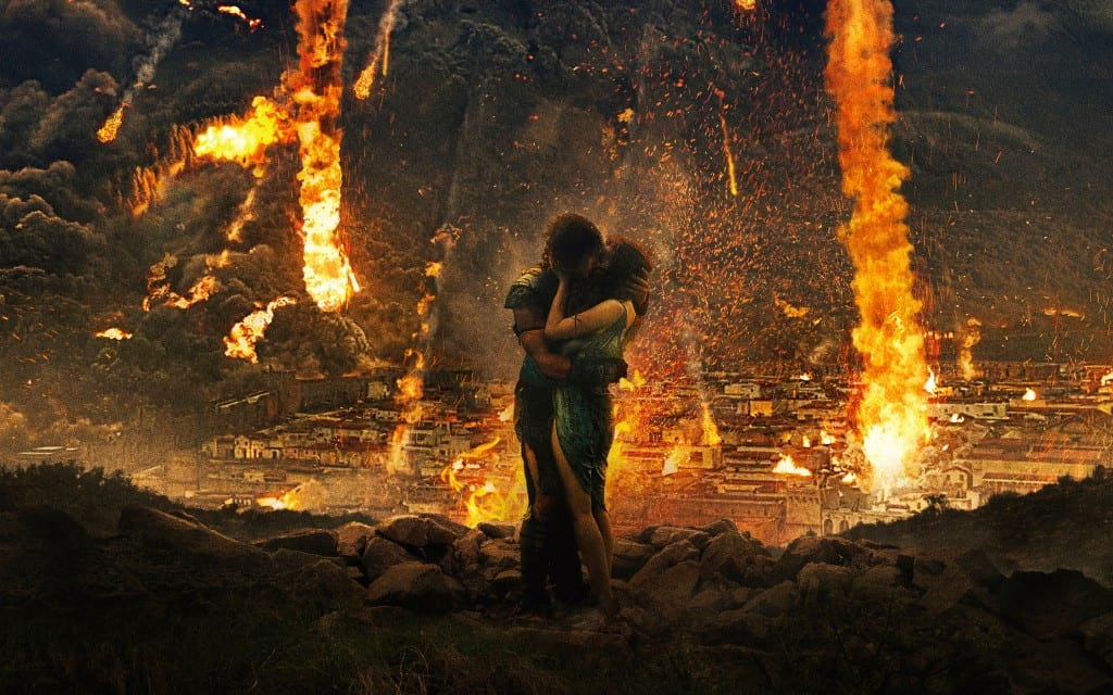 In the foreground a couple embrace and kiss standing on rubble. behind them Pompeii burns and smoulders