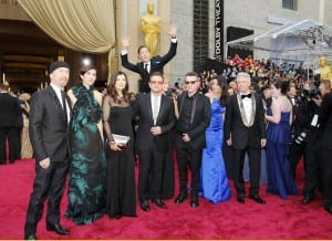 U2 posing for a photo on the red carpet at the Oscars 2014, with Benedict Cumberbatch jumping up behind them.