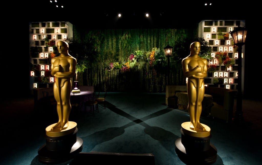 Two giant Oscars statuettes stand in a dimly lit room in front of tables, chairs and decorations.