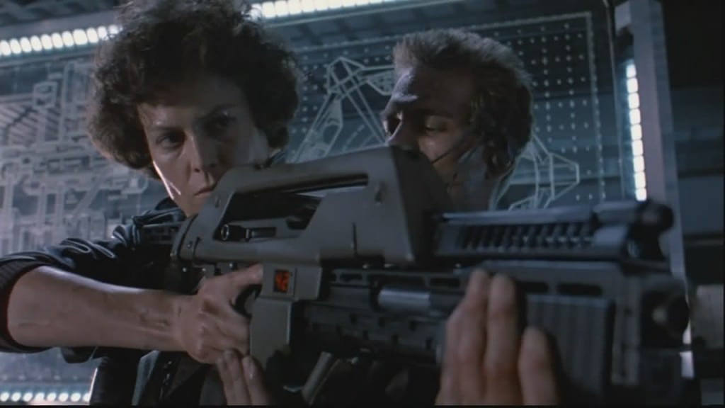 Image shows protagonist Ellen Ripley brandishes a Pulse Rifle in the movie Aliens.