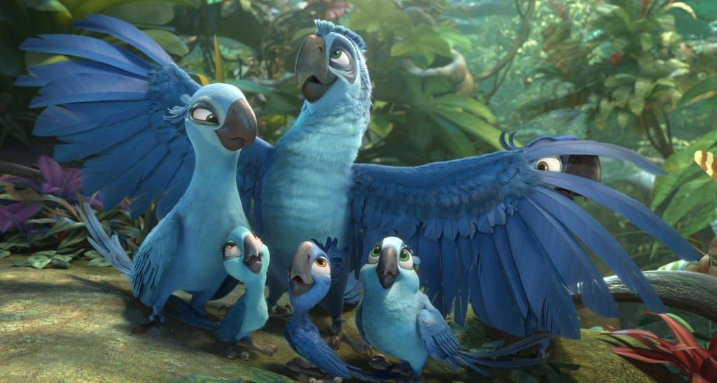 Image shows a still from the upcoming animated movie, Rio 2. The still shows 5 blue birds sitting together as a family in the jungle.