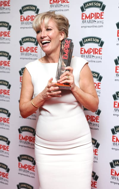 Emma Thompson posing with her Empire Award in front of a white background with the Empire Logo printed on it.