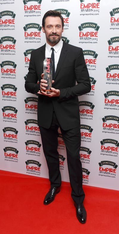 Hugh Jackman posing with his Empire Award in front of photographers.