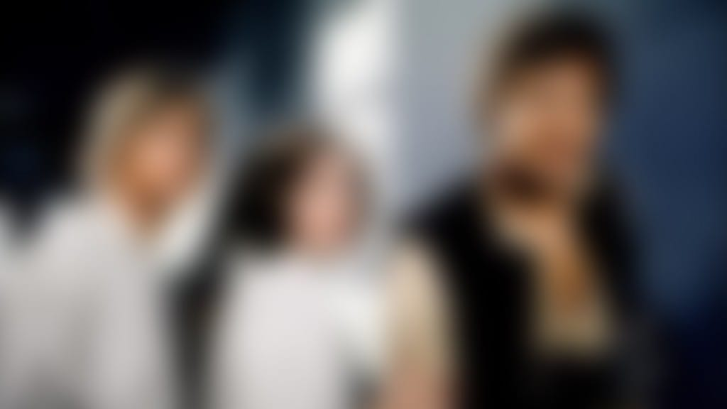Image shows actors, harrison ford, carrie fisher and mark hamill on the set of star wars. The image is blurred.