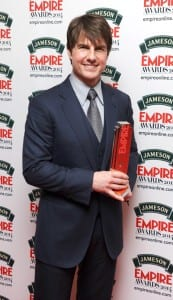 Tom Cruise holding his Empire Award in front of a white background with the Empire logo printed on it.