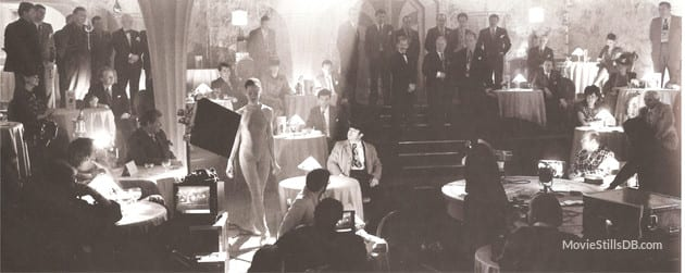 A young woman (Betsy) stands in the spotlight in a dim bar, performing as Jessica Rabbit, her male co-stars stare in awe