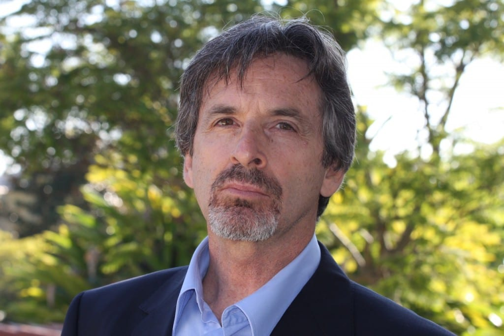 The actor Robert Carradine stood in a forest.