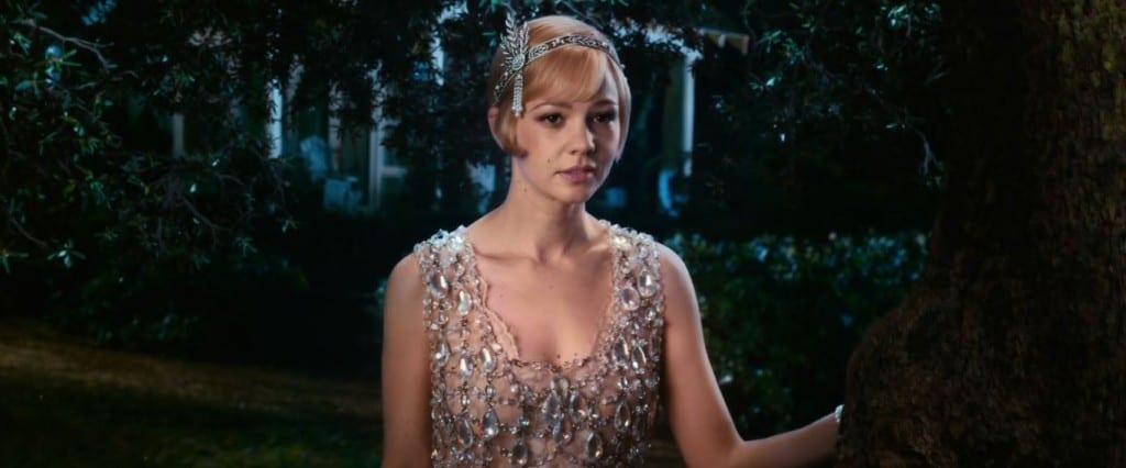 Carey Mulligan as Daisy Buchanan looks into the distance wearing a stunning crystal Prada dress and Tiffany & Co headpiece