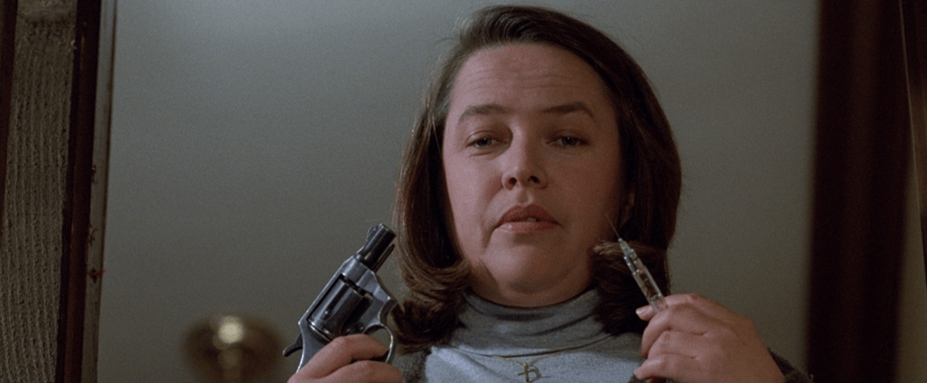 Annie Wilkes holding a revolver and a syringe.
