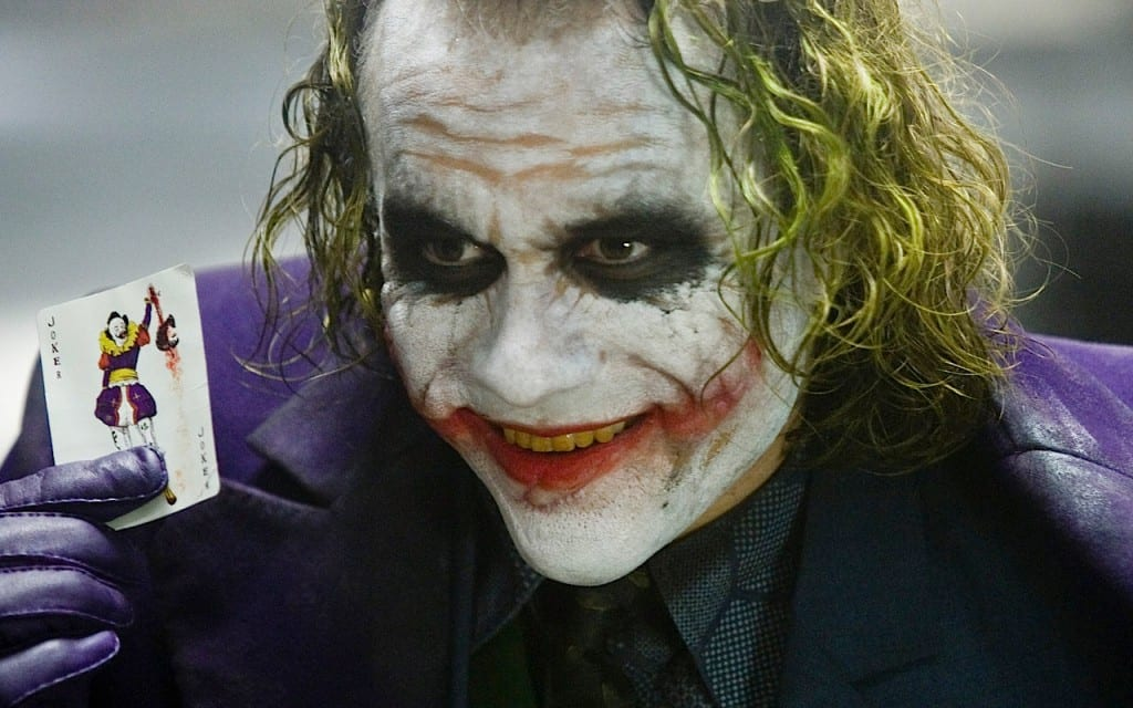 Heath Ledger's Joker holding a Joker playing card.
