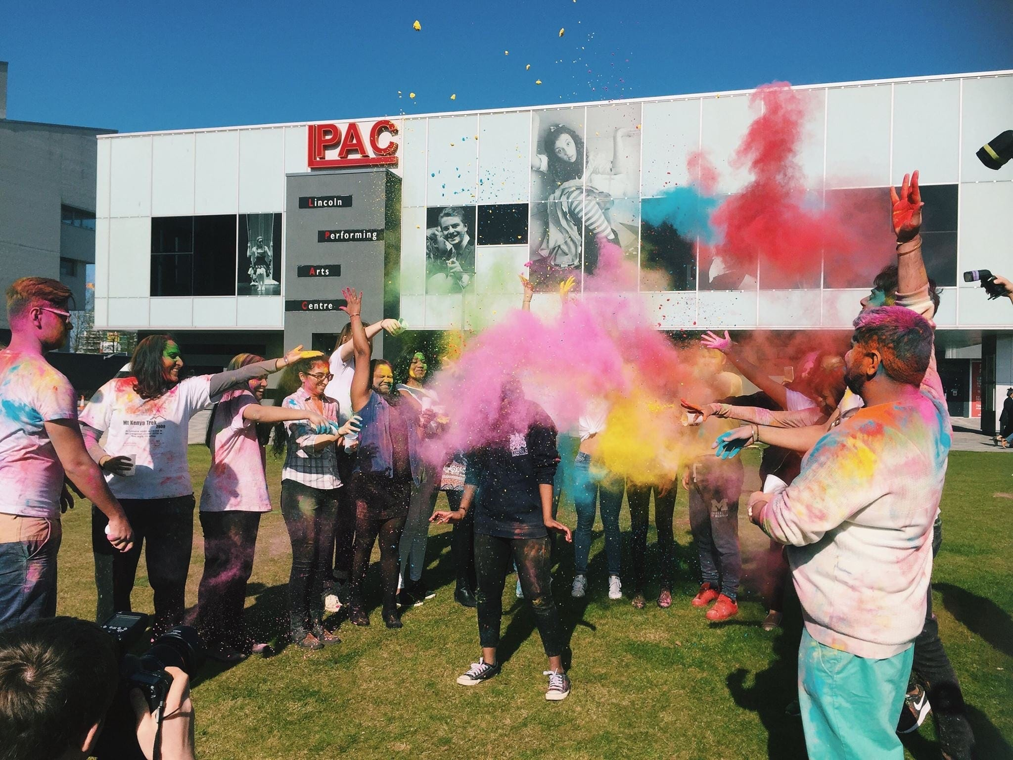 Learning at Lincoln - Group of University of Lincoln students throwing multicoloured paint powder at Holi celebration.