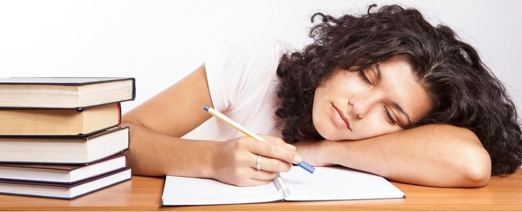 A woman writing with a pencil in a book. She is resting on her arm in a sleeping position.