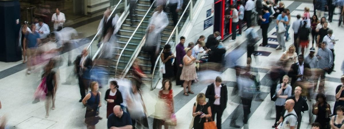 A picture of a shopping centre. Most of the people are blurred.