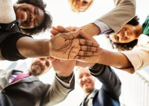Group of people in circle with hands of top of each other