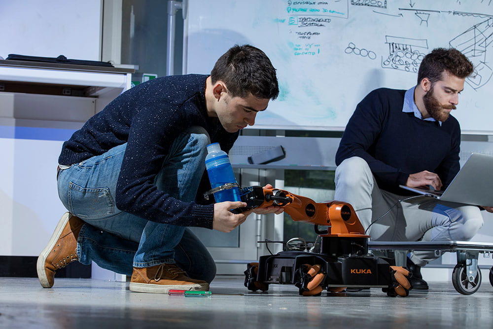 Students kneeling down inspecting a robot.