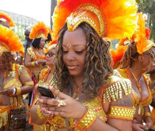Trinidadian woman using mobile phone at a carnival (Photo by Daniel Miller)