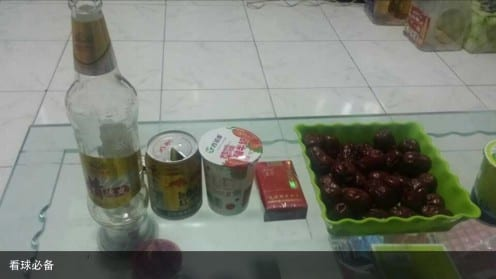 "Post young man from North China fieldsite on his WeChat profile. Caption reads ""Essential preparation for watching football."" From left to right is beer, red bull, yoghurt, cigarettes and plate of red dates."