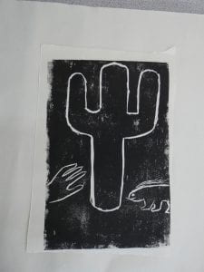 A black and white lino cut depicting a cactus, a hand reaching towards it and a porcupine looking on.