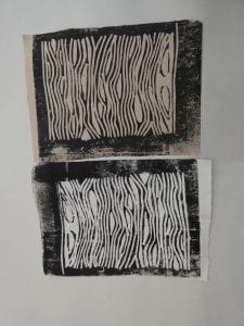 Two black and white lino cut prints, side to side, depicting the same close-up pattern of wood grain.