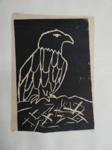 A black and white lino cut print of the profile of an eagle, standing a the edge of its nest.