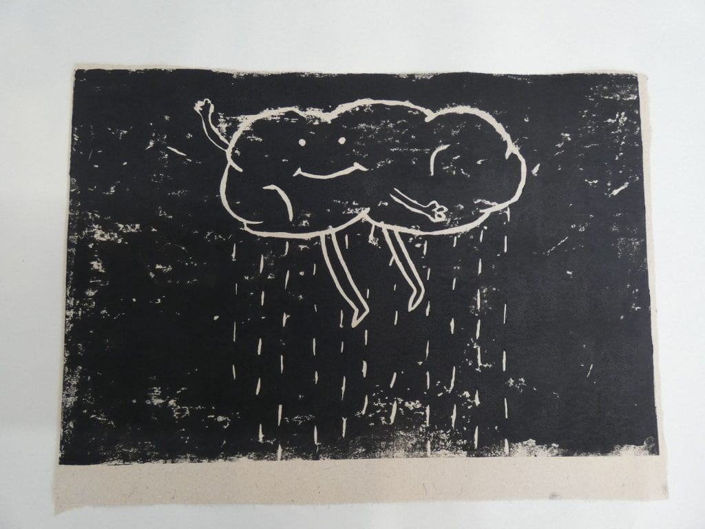 A black and white lino cut of a personified cloud (with a smiley face), distributing rain.
