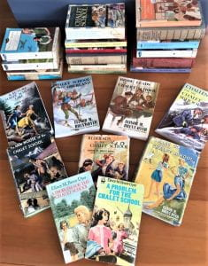 A collection of 'Chalet School' hardbacks and paperbacks in various states of repair