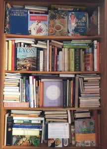 wooden shelves crammed full of books from Laurent Cruveillier's cookbook collection