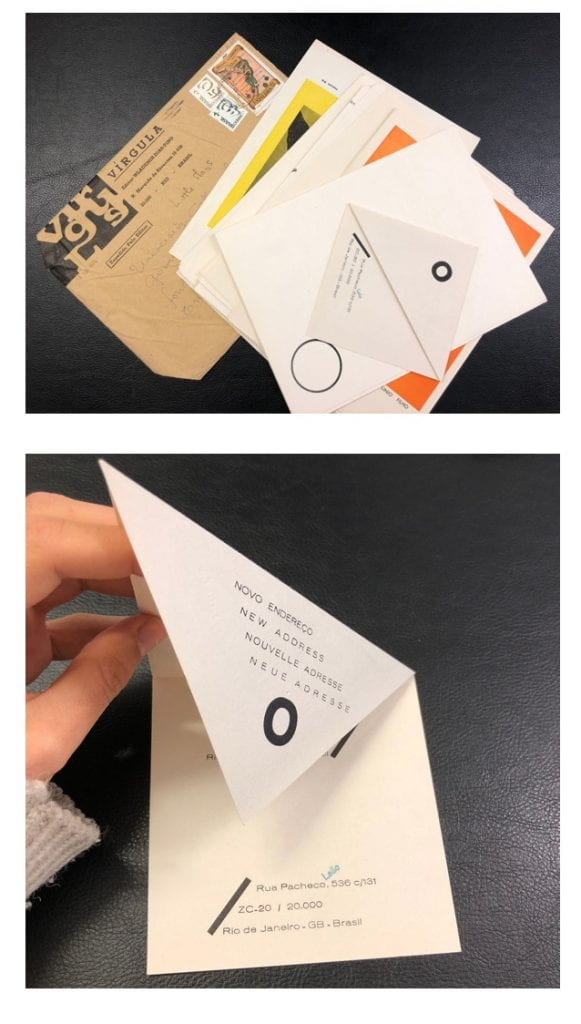 A hand unfolding a paper envelope from Virgula magazine