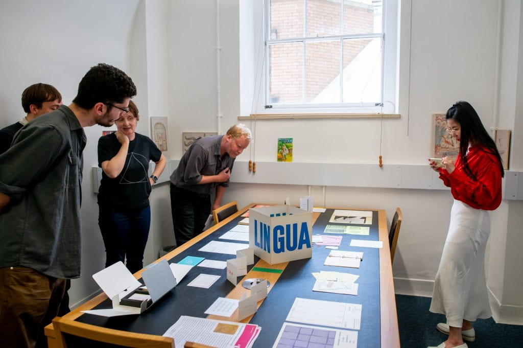 Four visitors and a member of staff stand over a table in UCL Special Collections' South Junction Reading Room, looking at collection items from our Poetry Store collection. The items are colourful and vary in format, some folded and with bold print, others non-standard sizes.
