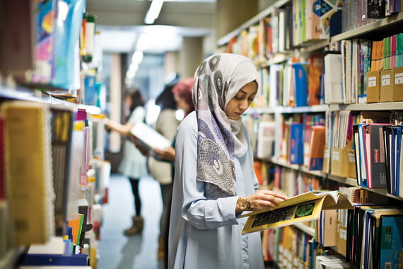 A student looks for resources in a library. Shelves laden with colourful books line the edges of the photograph as she reads a book.