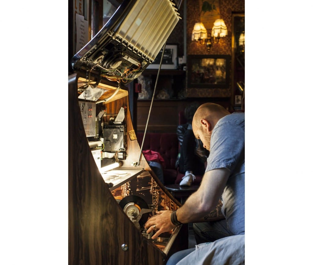 Bradley's Spanish Bar in 2014; fixing the jukebox (© Historic England, Chris Redgrave)